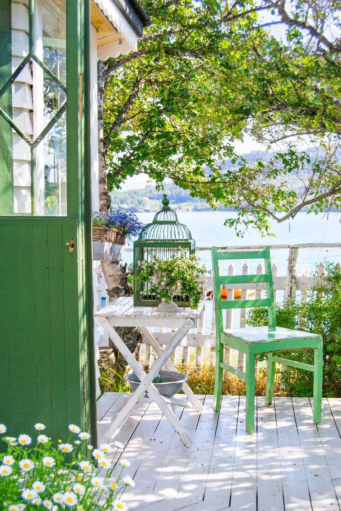 Hvitmalte gjerder, et vell av blomster, lysthus og koselige sitteplasser. Med en slik hage ved sjøen har ikke eierne behov for å reise noe annet sted.