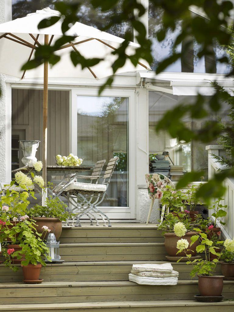 Med blomster både på tekstiler og i krukker får uteplassen et romantisk preg. Krukker med pelargonia, hortensia og andre sommerblomster i overflod.
