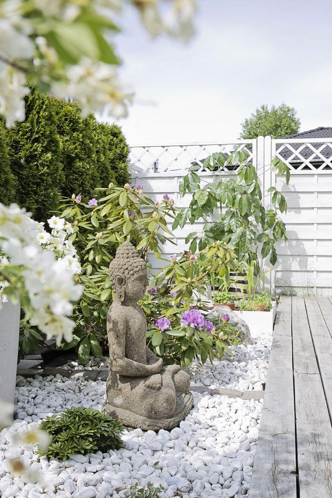 Terrassen ligger på bakkeplan med direkte utgang fra stuen. Hvite steiner, grønne planter og jernmøbler sender tankene mot varmere strøk.