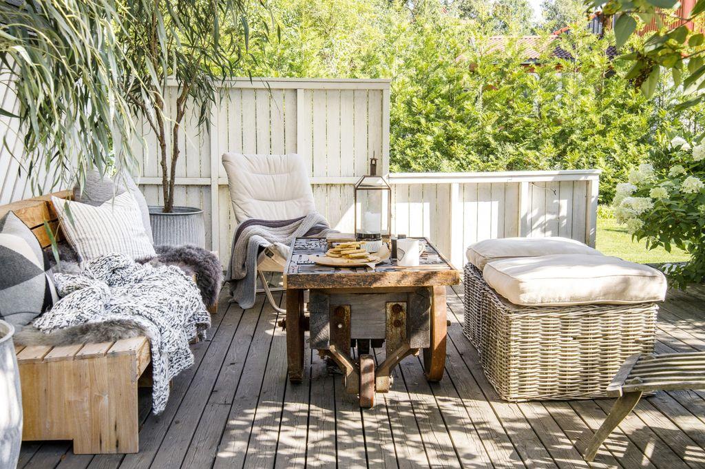 På denne terrassen møtes slitt tre, myke tekstiler og rå detaljer. Her er det den rustikke stilen som gjelder.