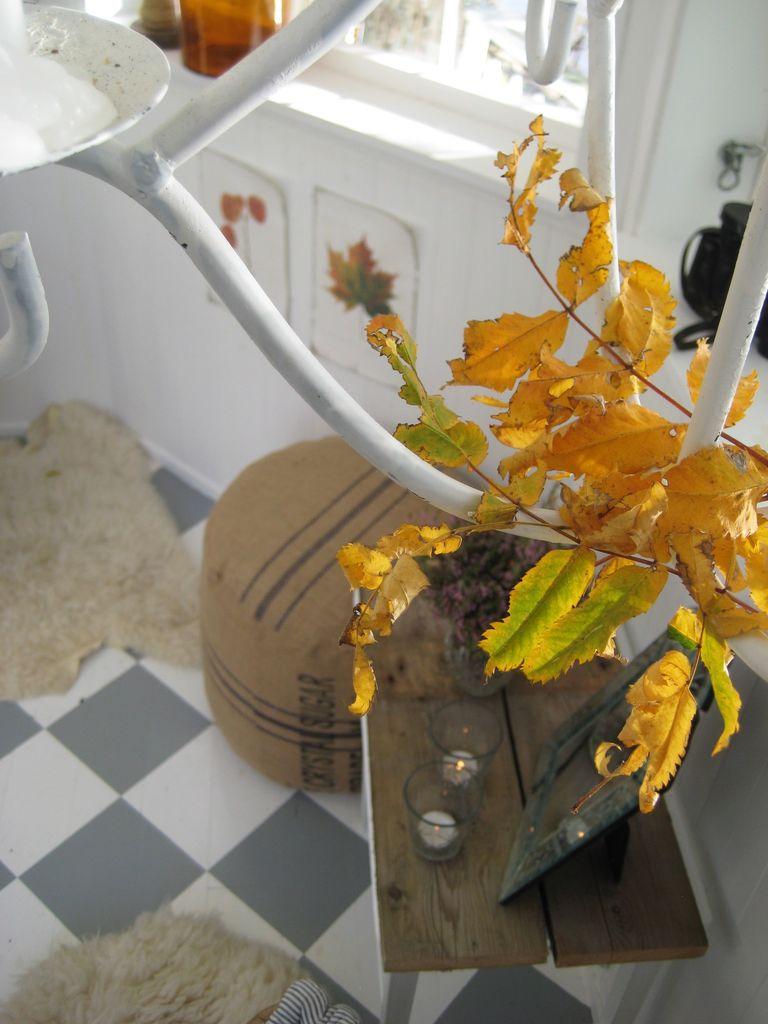 Lysekronen som henger i taket er også kledd opp til høst. De gulgrønne bladene står i fin kontrast til det brune i interiøret her inne. Pynt til høst i lysthuset.