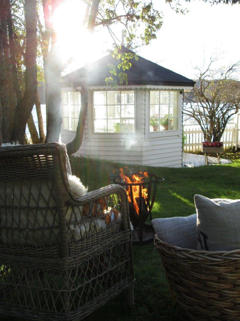 Solstrålene skinner om kapp med flammene. Bål i hagen hører med om høsten. Her kan tørt høstløv som har falt ned på plenen brennes.
