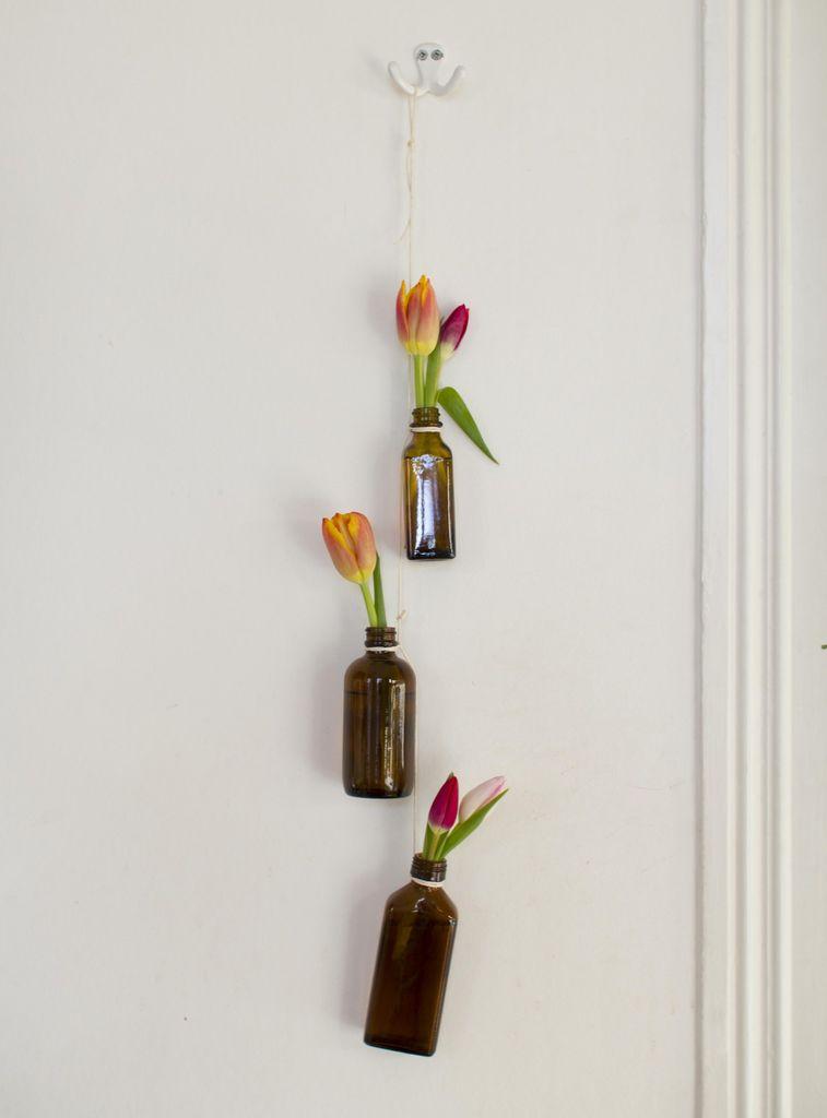Heng blomstene rett på veggen i minivaser festet med hyssing.