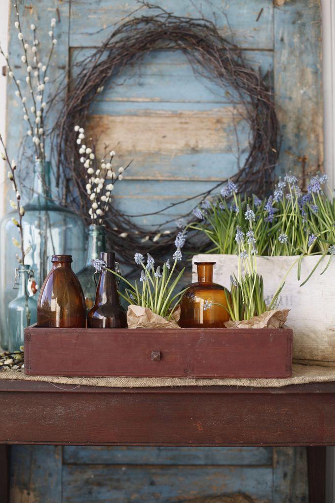 Ei skeiv, gammal blå dør og et brunt, slitt trebord skaper rammen for pynten. Den blå vedkassa under bordet plukker opp fargen til perleblomstene i den gamle kassa på bordet.