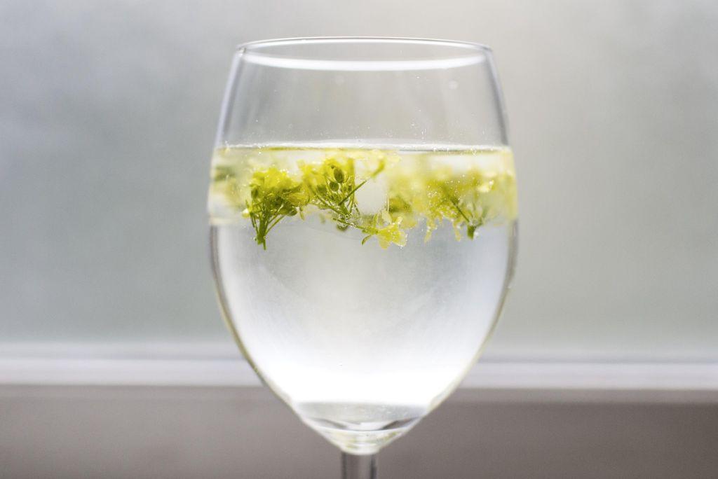 Lag en sommerlig og festfin drink med isbiter med spiselige blomster.